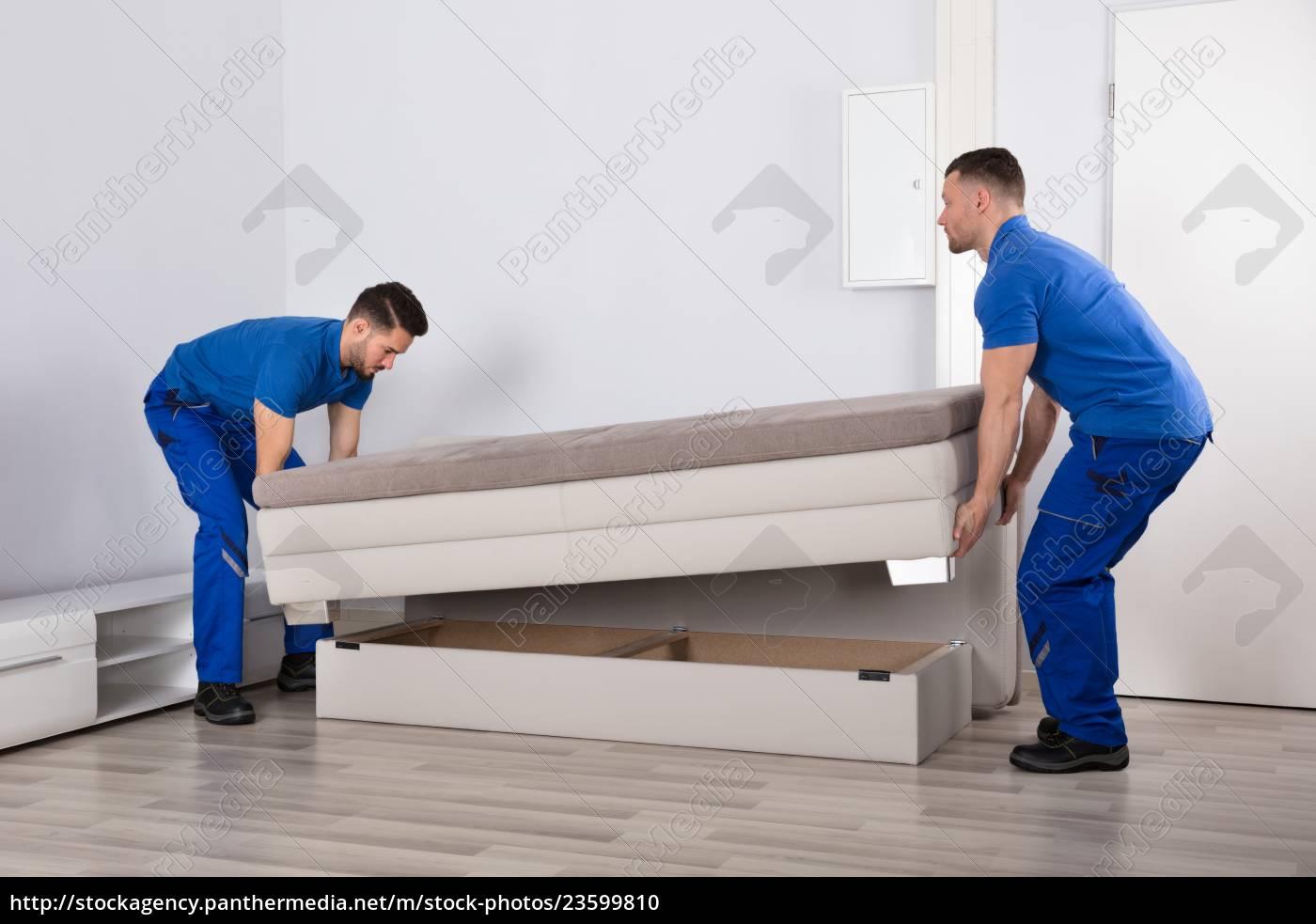 two, men, holding, sofa, in, living - 23599810