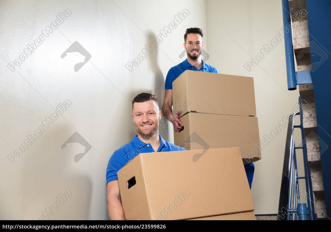 two, movers, carrying, cardboard, boxes, on - 23599826