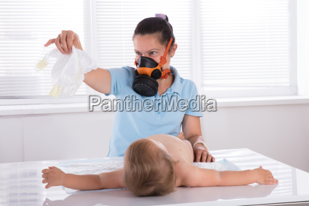 woman, changing, smelly, nappy, of, her - 23599878
