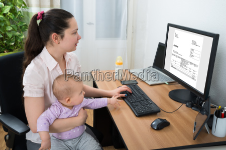 woman, checking, bill, on, computer - 23599842