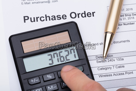 person using calculator on purchase order