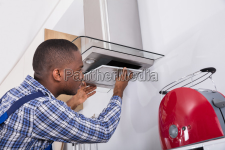 african male fixing kitchen extractor filter