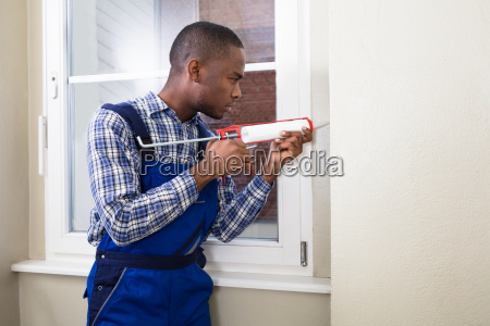 male worker applying silicone sealant