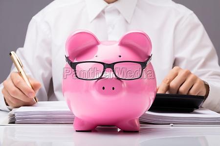 businessman, calculating, tax, with, piggybank - 23600668