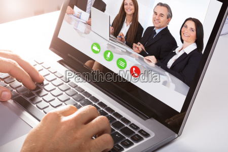 businessperson's, hand, video, conferencing, with, colleagues - 23600716
