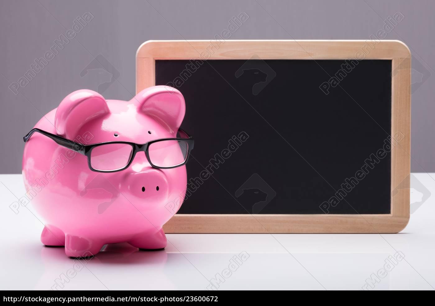 piggybank, with, eyeglasses, near, blank, slate - 23600672