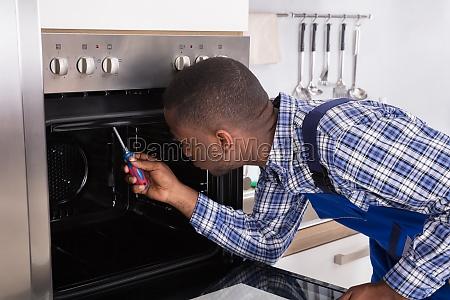 repairman, fixing, kitchen, oven - 23600738
