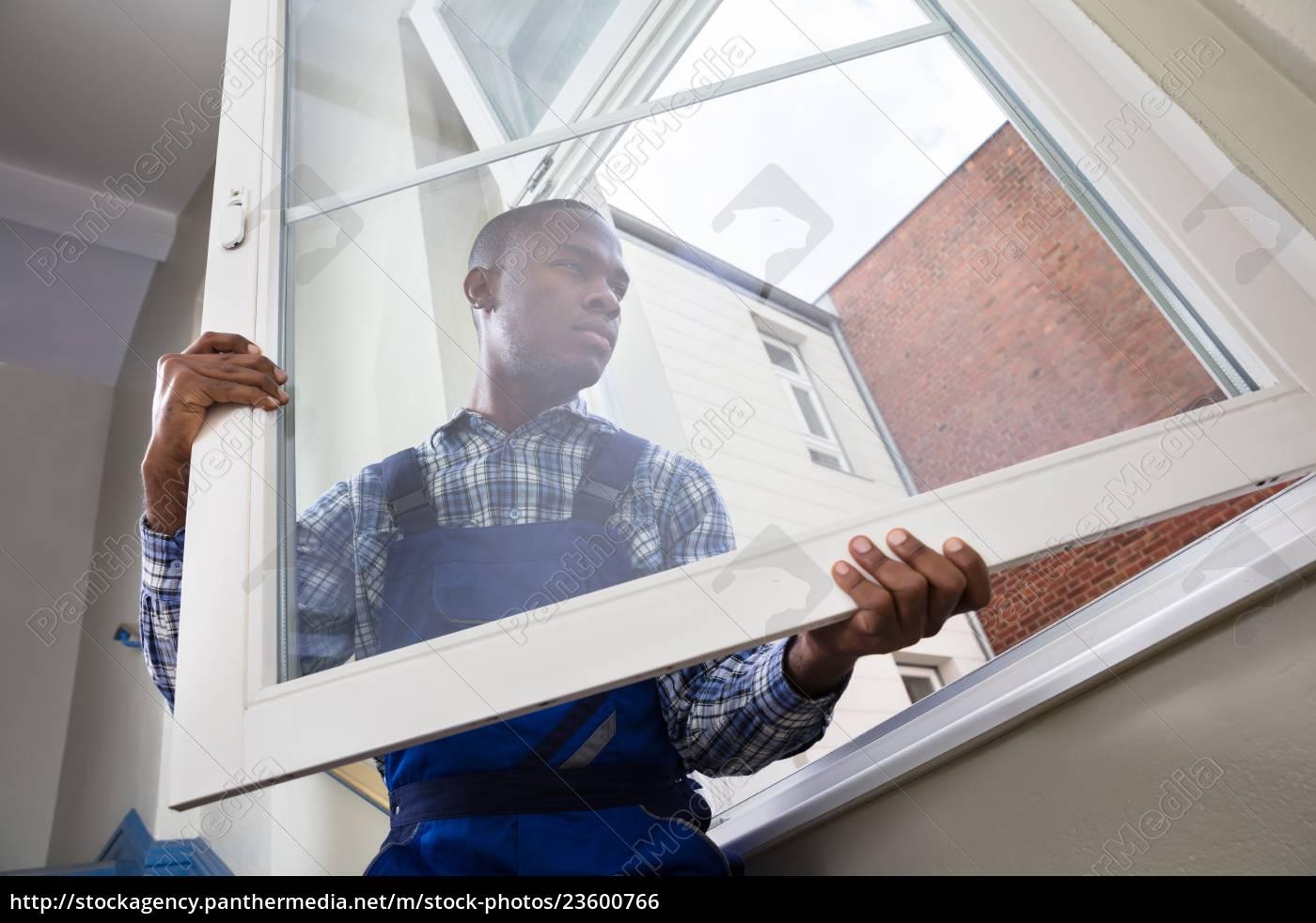 repairman, in, overalls, installing, window - 23600766