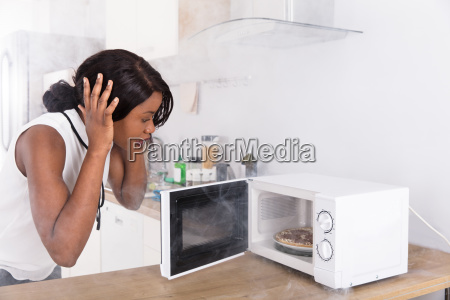woman, looking, at, burnt, pizza, in - 23600614