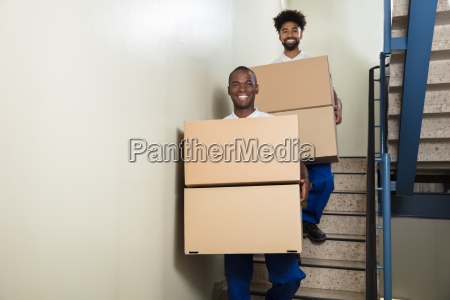 portrait of two movers holding cardboard