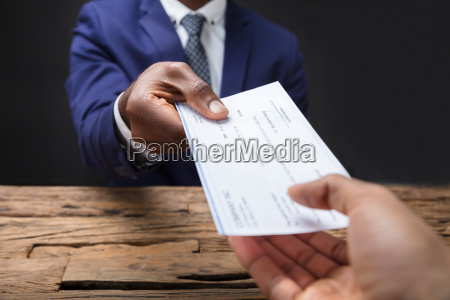 businessman, giving, cheque, to, his, colleague - 23601298