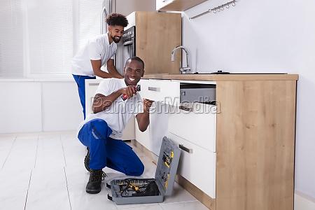 repairmen, fixing, the, wooden, cabinet, in - 23601332