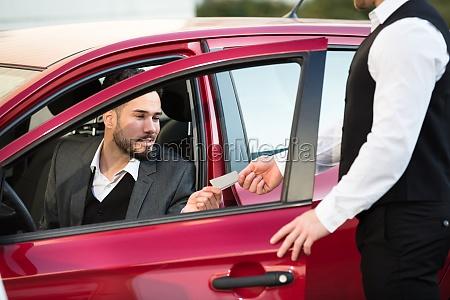 valet, giving, receipt, to, businessperson, sitting - 23601444