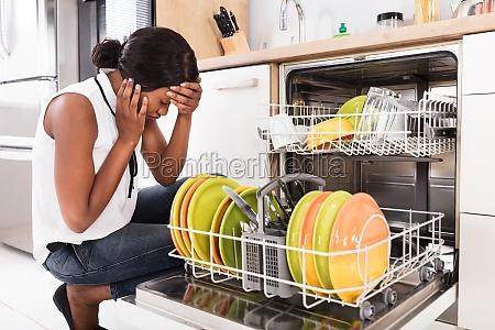 sad woman crouching near dishwasher