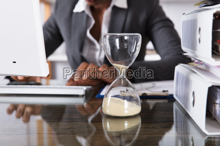 close-up, of, hourglass, on, desk - 23602118