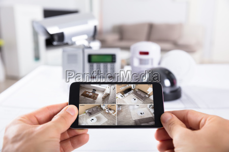 person, holding, mobile, phone, with, cctv - 23602042