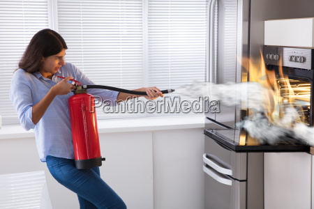 woman using fire extinguisher to put