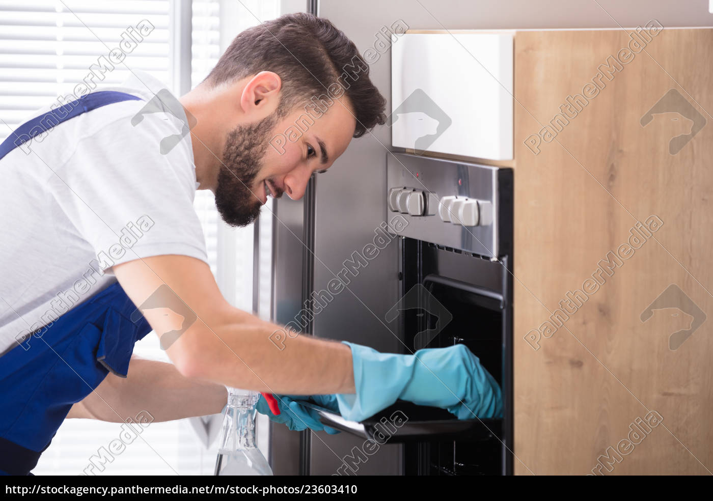 janitor, cleaning, oven, in, kitchen - 23603410