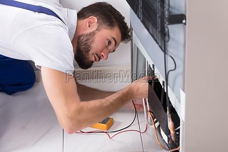 male, technician, examining, refrigerator - 23603458