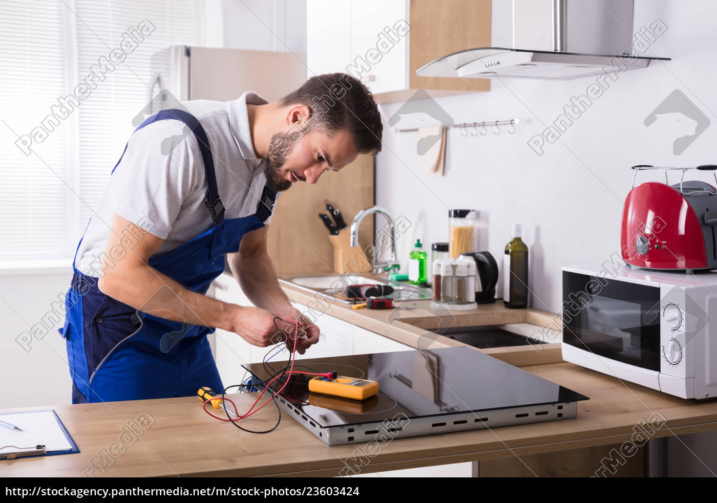 technician, repairing, induction, stove, in, kitchen - 23603424