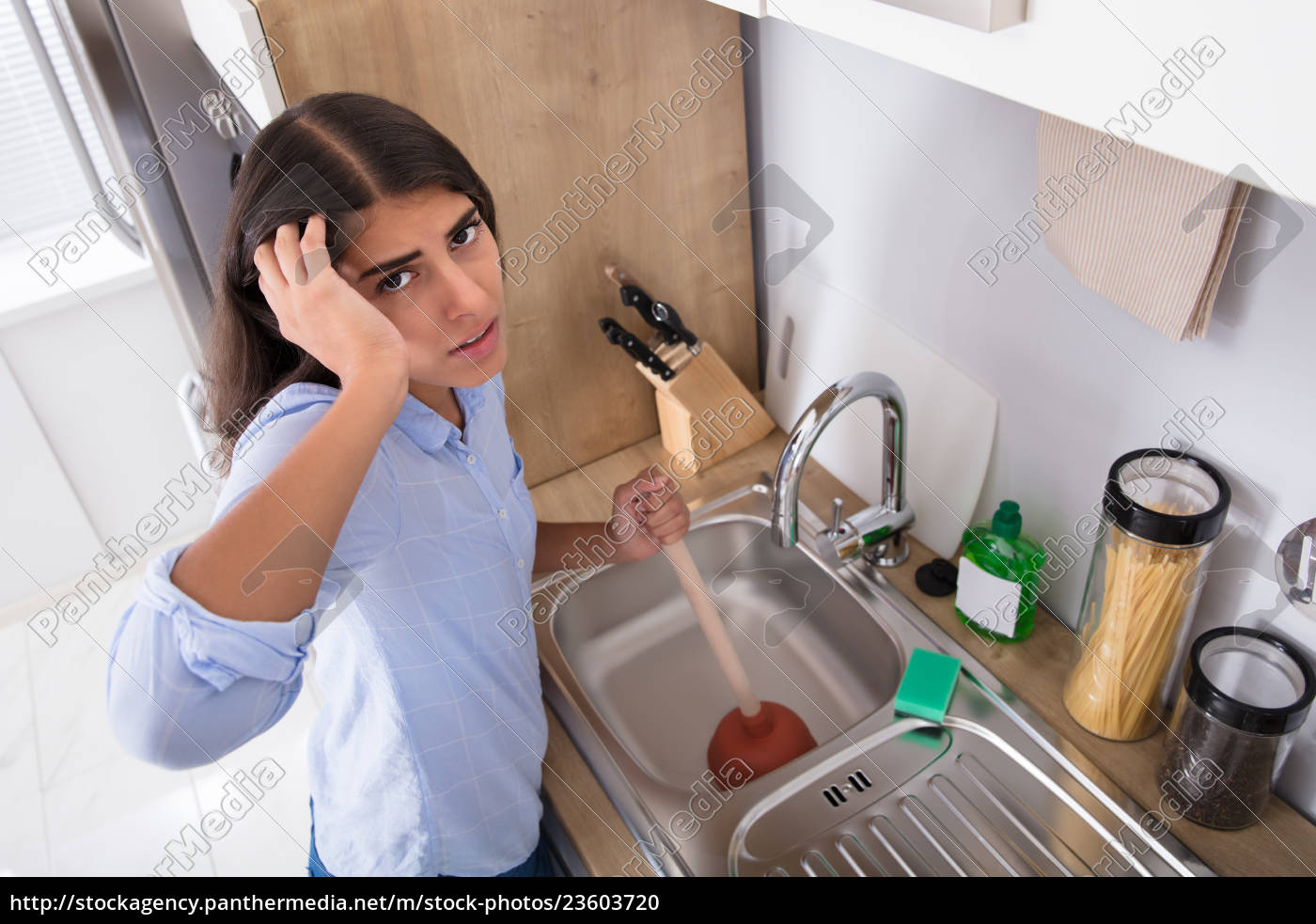 unhappy, woman, using, plunger, in, clogged - 23603720