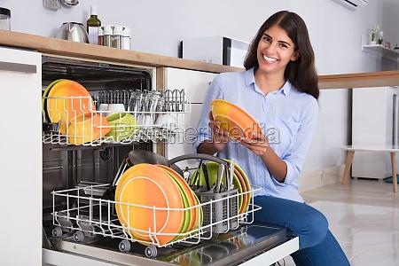 woman, arranging, plates, in, dishwasher - 23603652