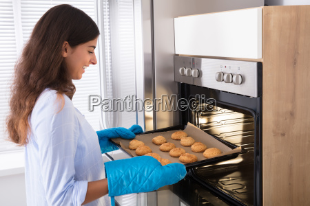 woman, taking, out, tray, of, baked - 23603714