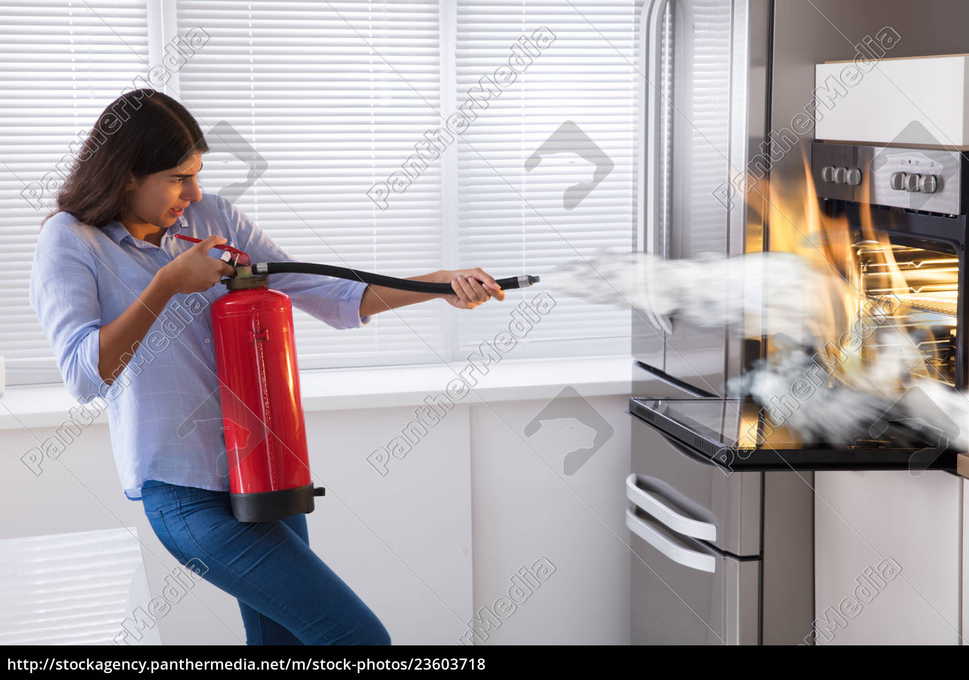 woman, using, fire, extinguisher, to, put - 23603718