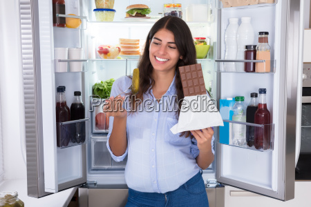 young, woman, eating, chocolate - 23603566