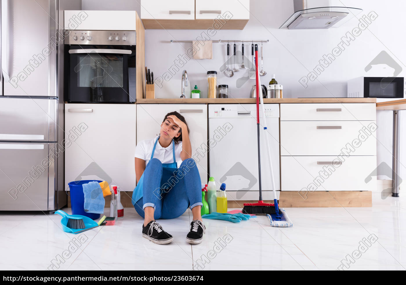 young, woman, sitting, on, kitchen, floor - 23603674