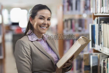 smiling hispanic woman holding book in