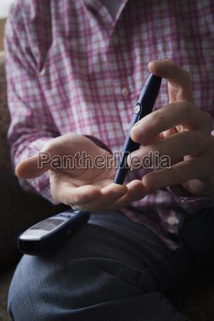 diabetic hispanic man checking blood in