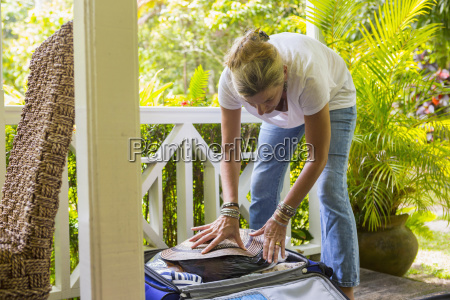 caucasian woman packing suitcase on porch