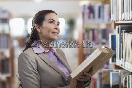 pensive hispanic woman holding book in