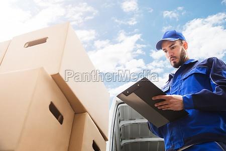 male worker standing near cardboard box