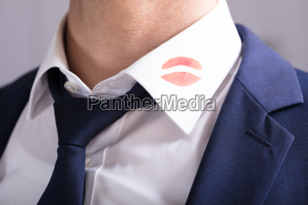 businessman, with, lipstick, kiss, marks, on - 23610496