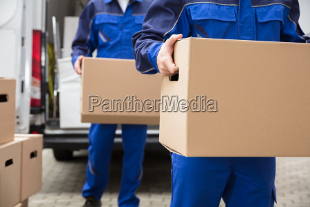 close-up, of, two, movers, carrying, cardboard - 23610674