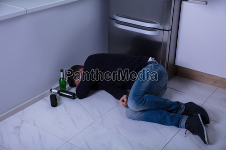 man, lying, on, floor, in, kitchen - 23610310