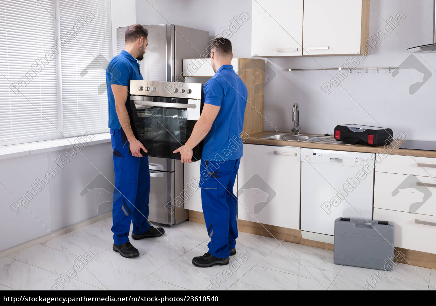 two, men, fixing, oven, in, kitchen - 23610540