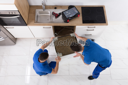 two, movers, placing, dishwasher, in, kitchen - 23610546