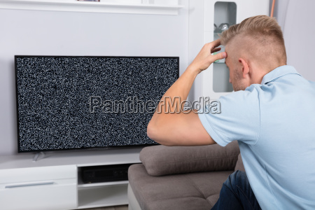 man in front of television with