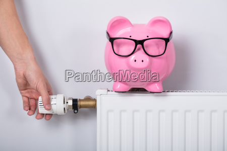 man's, hand, adjusting, thermostat, with, piggy - 23618260