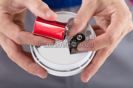 person's, hand, inserting, battery, in, smoke - 23618090
