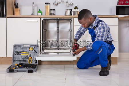 repairman fixing dishwasher