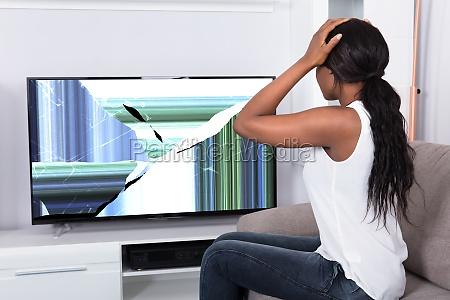 upset woman looking at broken television