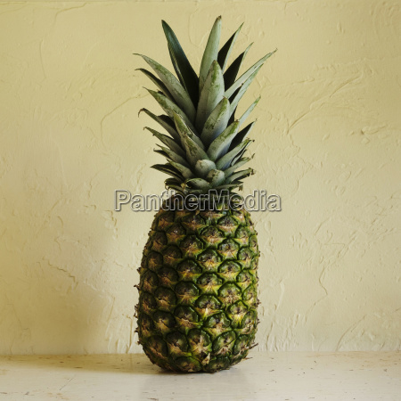 fresh pineapple against textured wall