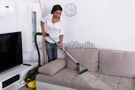 african, woman, cleaning, sofa, with, vacuum - 23620374