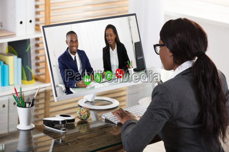 businesswoman, videoconferencing, with, her, colleagues, on - 23620352