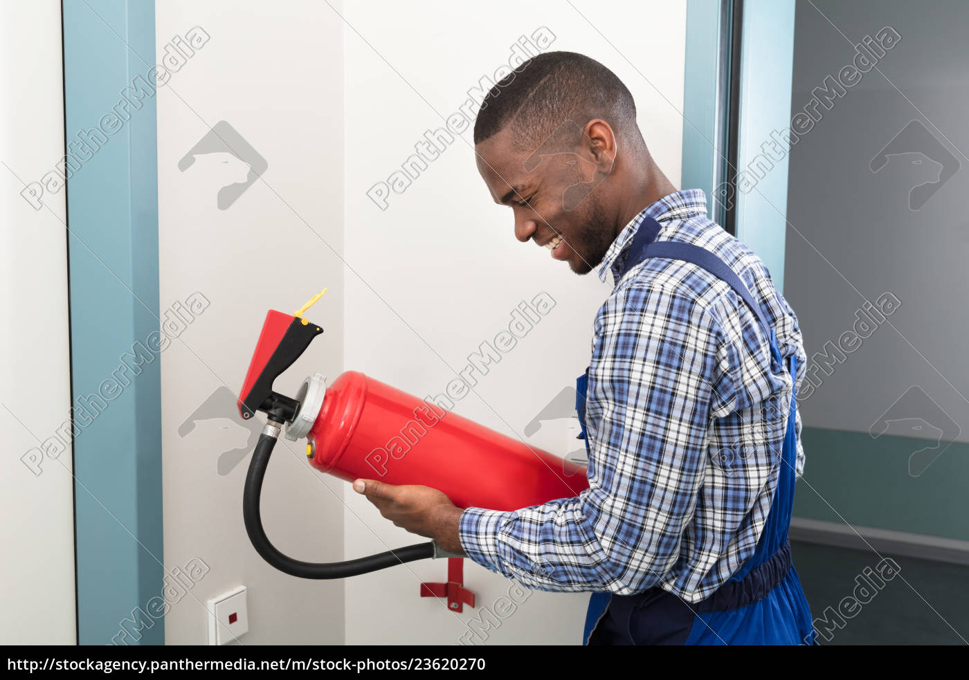 male, african, professional, holding, fire, extinguisher - 23620270