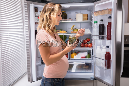 pregnant, woman, eating, pickle, from, jar - 23620364